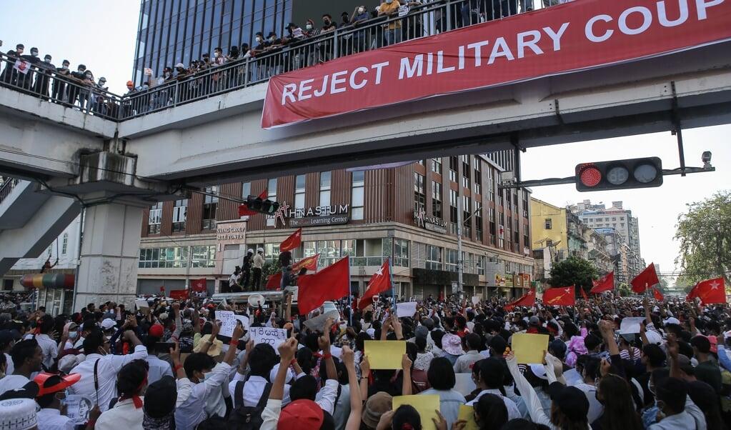Een lange sliert demonstranten trekt door de straten van Yangon. 'Moet je kijken hoeveel mensen de straat op zijn gegaan. Neem je dit wel allemaal op?'  (beeld afp)