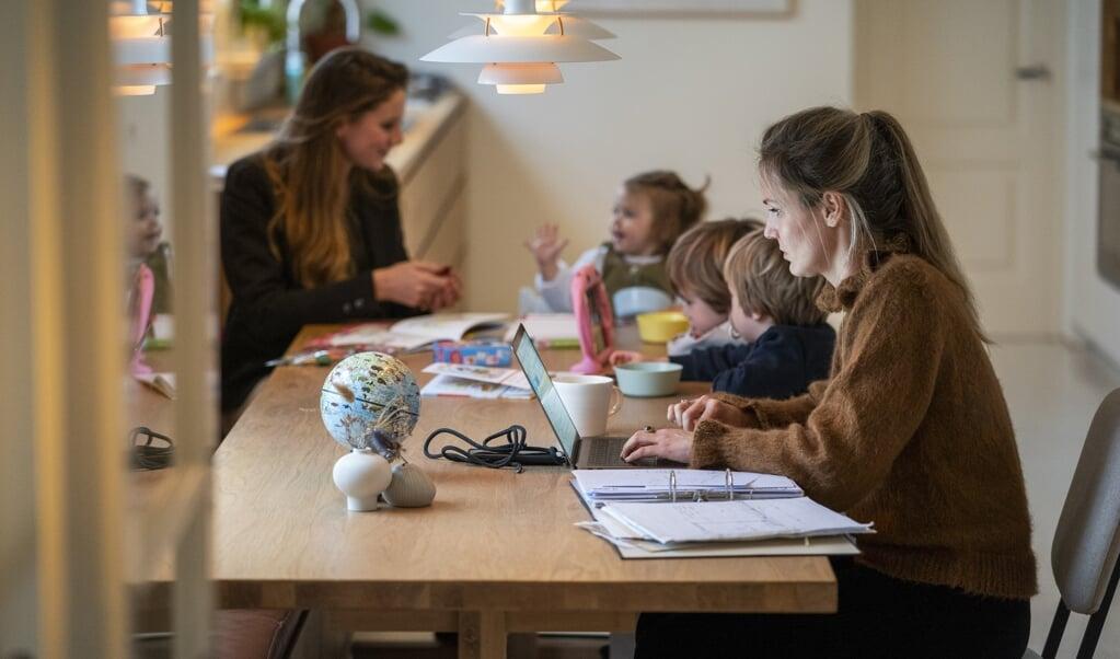 Een gezin met een oppas van een Amsterdamse oppasservice. Ouders die vanwege de lockdown thuiswerken en hun kinderen moeten helpen met thuisonderwijs schakelen steeds vaker een oppas in.  (beeld anp / Jeroen Jumelet)