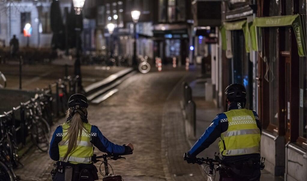 Handhavers lopen bij het ingaan van de avondklok door het centrum van Utrecht.  (beeld anp / Jeroen Jumelet)