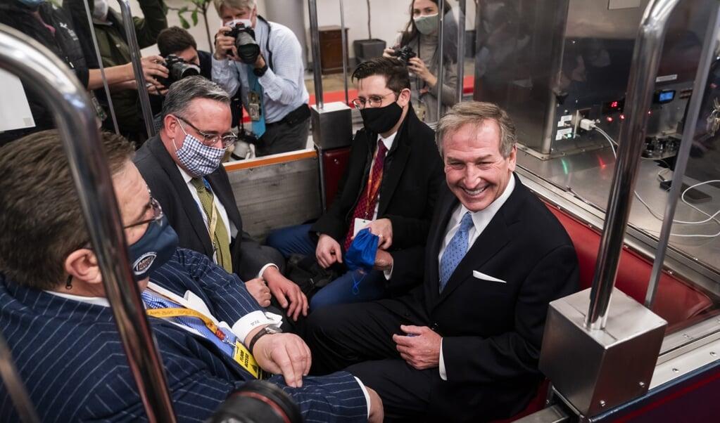 Advocaat Michael van der Veen samen met andere leden van Trumps verdediging in de 'Senate subway', de ondergrondse verbinding van senaatskantoren en het Capitool, na de vrijspraak van Trump.  (beeld epa / Jim lo Scalzo)