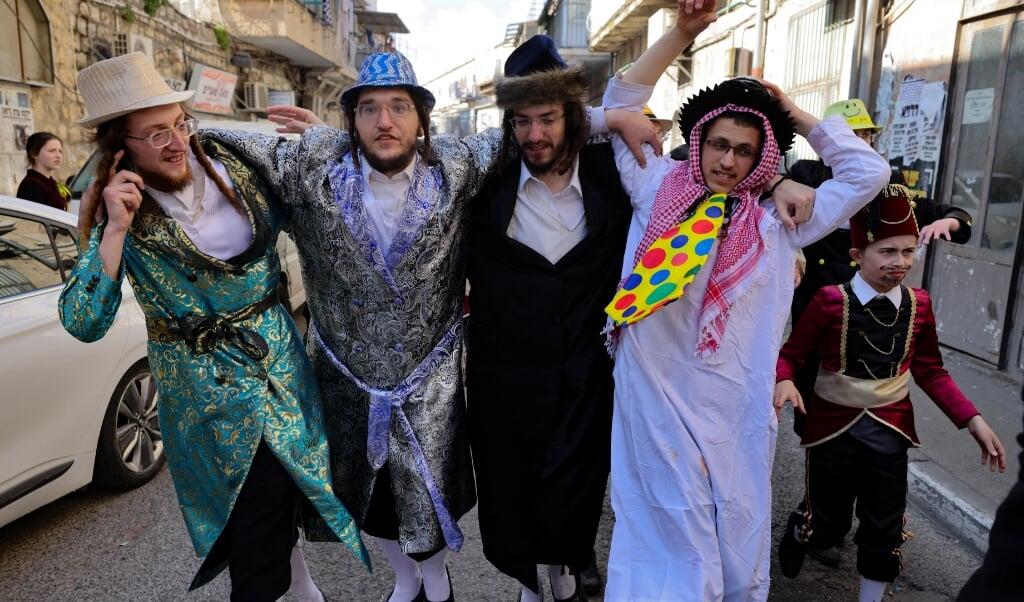 2021-02-28 11:30:34 Orthodox Jewish men, dressed in costumes to celebrate Purim, are pictured in the neighbourhood of Mea Shearim in Jerusalem, on February 28, 2021.   menahem kahana / AFP  (beeld afp / Menahem Kahana)