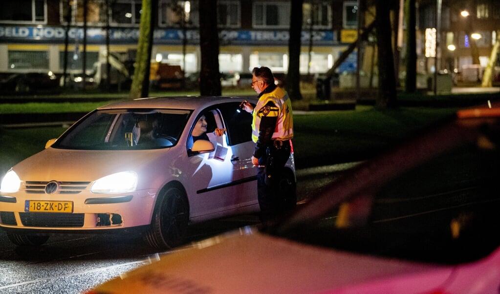 De politie controleert automobilisten op het Zuidplein in Rotterdam-Zuid. Vooral jongeren en jongvolwassenen hebben moeite met de avondklok.  (beeld anp)