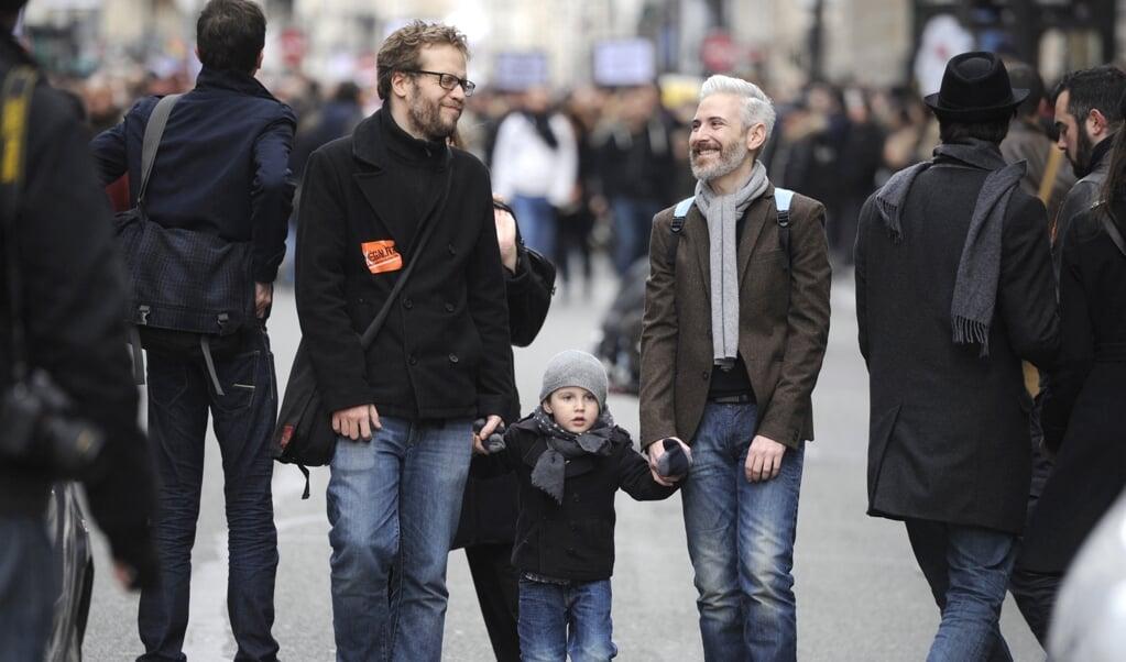 Twee mannen en een kind tijdens een protest voor lhbt-rechten in Parijs, 2012.   (beeld afp / Fred Dufour )