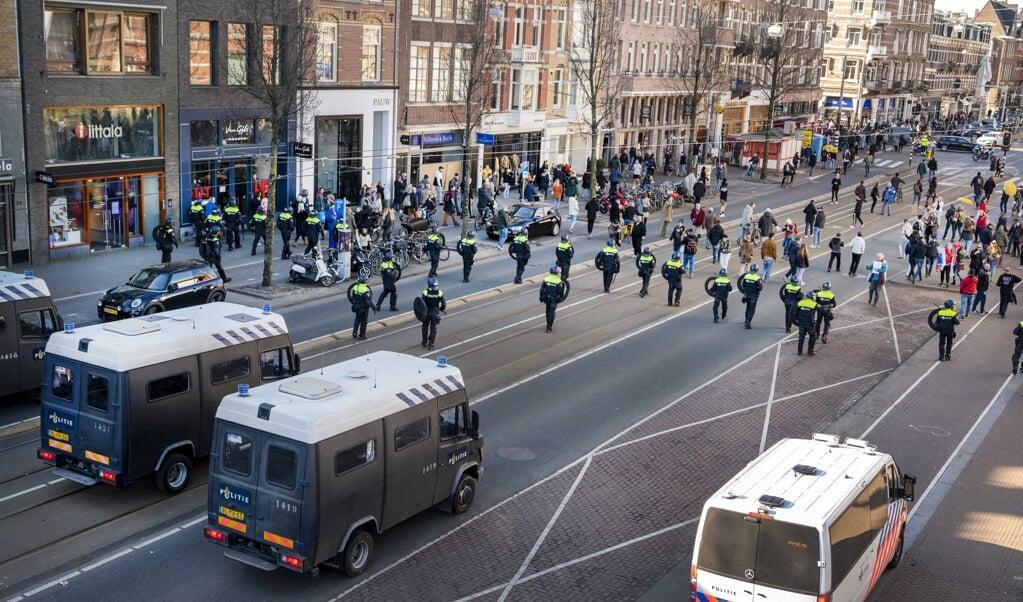 Op last van de Amsterdamse driehoek (burgemeester, politie, justitie) werd zondagmiddag het Museumplein leeggeveegd toen demonstranten weigerden het plein te verlaten. Ze protesteerden tegen de huidige coronamaatregelen.   (beeld epa / Evert Elzinga)
