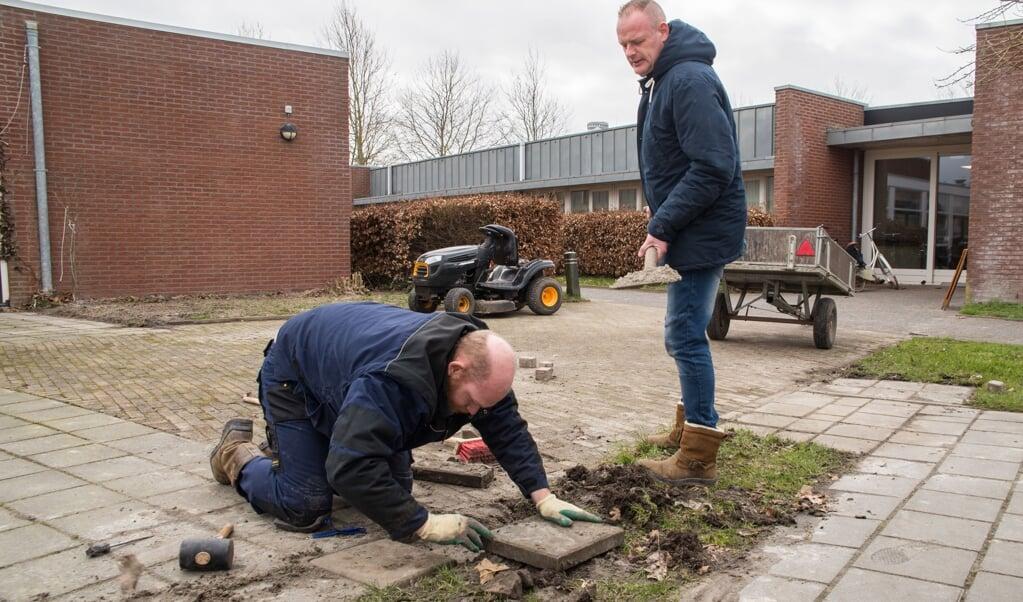 Dennis Booms (links) legt een tegel, terwijl Marten Dohmeijer hem helpt.  (beeld Hans-Lukas Zuurman)