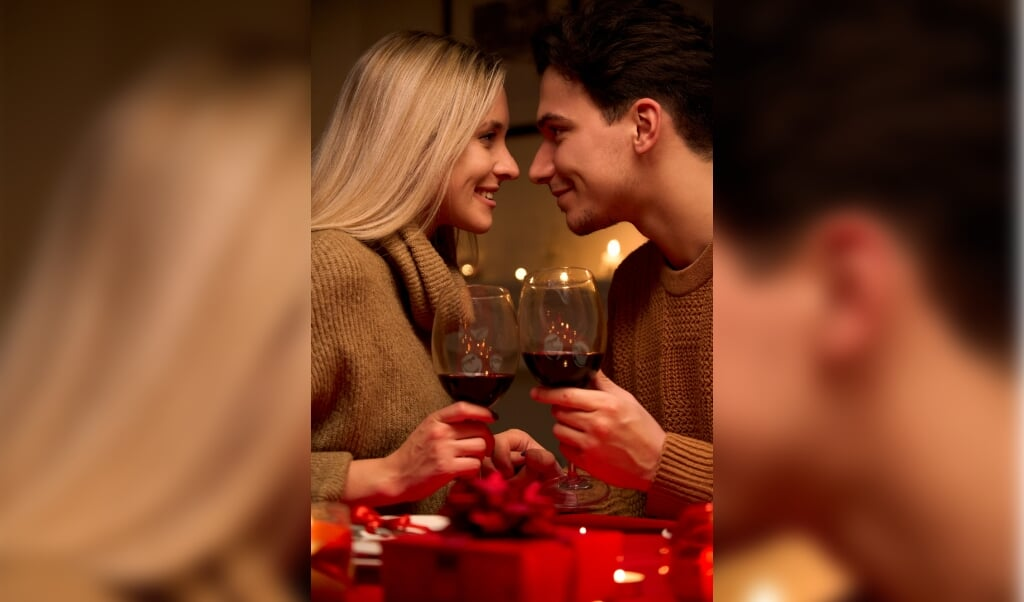 Happy young couple in love bonding, holding glasses, drinking wine, enjoy tender moment together celebrating Valentines day having romantic dinner date with candles sit at home table or in restaurant.  (beeld Getty Images/iStockphoto)