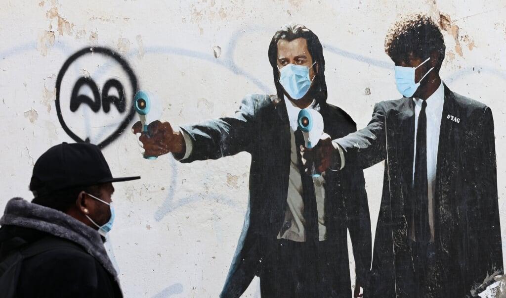 Een man in de Israëlische stad Tel Aviv loopt langs een muurschildering waarop de  Amerikaanse acteurs John Travolta en Samuel L. Jackson staan. In plaats van wapens hebben ze thermometers in hun handen, die gebruikt worden om tijdens de coronapandemie op afstand te meten of mensen verhoging hebben. <  (beeld afp / Emmanuel Dunand)