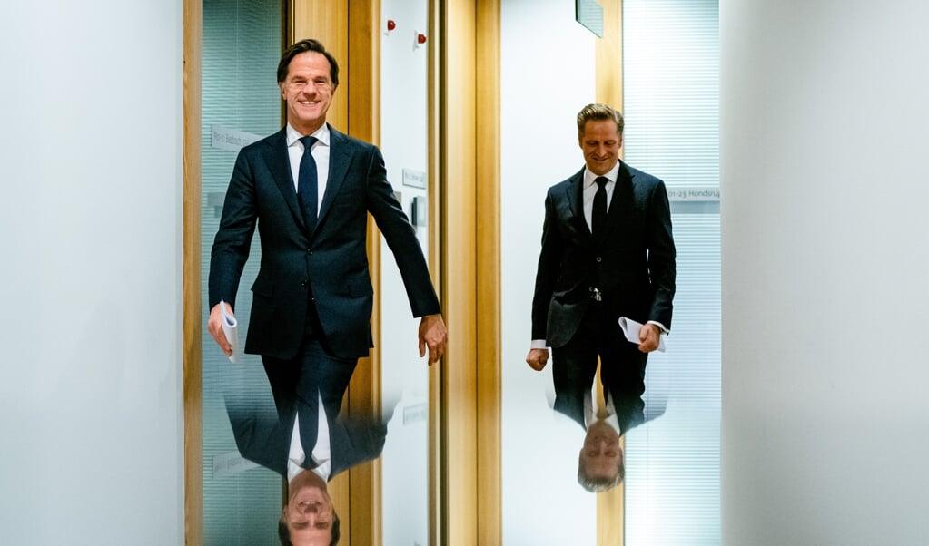 Demissionair premier Mark Rutte en demissionair minister Hugo de Jonge (Volksgezondheid, Welzijn en Sport) op weg naar de persconferentie over coronamaatregelen in Nederland.  (beeld anp / Bart Maat)