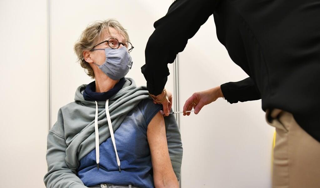 Een vrouw in Ede krijgt een vaccinatie met het AstraZeneca-vaccin.  (beeld anp / Piroschka van de Wouw)