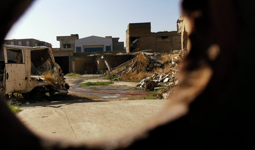 De binnenplaats van de Vrouwe van het Uur-kerk in Mosul, gezien door een kogelgat in de poort, ligt er troosteloos bij.  (beeld Jacob Hoekman)