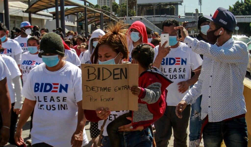 Een groep migranten in Tijuana, Mexico, doet een beroep op president Biden om hen toe te staan de Verenigde Staten in te mogen.  (beeld epa / Joebeth Terriquez)