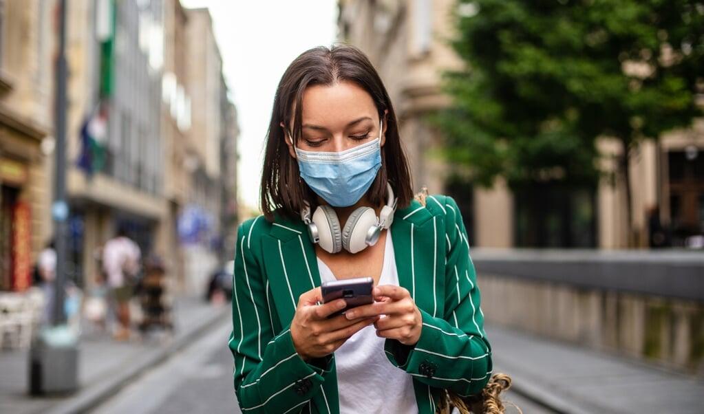 Mensen lopen tegenwoordig standaard met een telefoon in de hand, in connectie met iemand-op-afstand.  (beeld istock / Smiljana Aleksic)