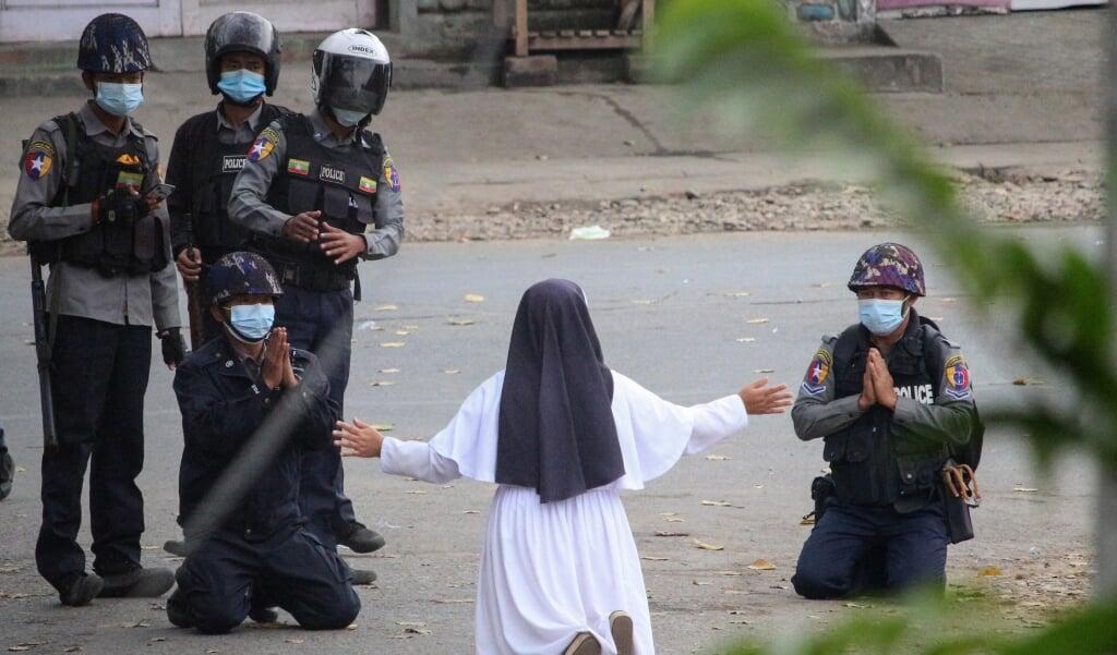 Zuster Tawng knielt voor politieagenten en smeekt hen te stoppen met schieten.  (beeld Handout / Myitkyina News Journal / afp)