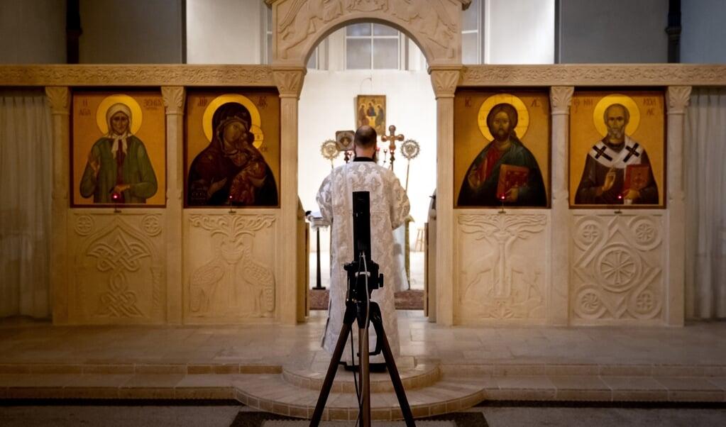 Een online viering in de Russisch Orthodoxe kerk in Amsterdam, gestreamed voor gelovigen thuis en passend bij het huidige niveau 'zeer ernstig'.  (beeld anp / Koen van Weel)