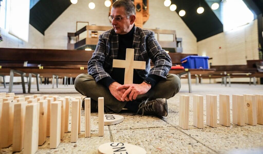 Dominee Ton van der Wekken legt aan de hand van vallende dominostenen de zondeval uit, en hoe Jezus de afstand heeft overbrugd.  (beeld Maarten Boersema)