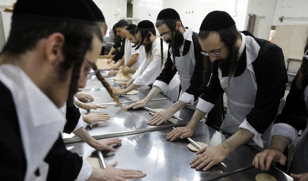Joden maken in een bakkerij matzes – brood dat niet gerezen is –  ter voorbereiding op Pesach, dat aflopen zaterdag begon.  (beeld Menahem Kahana)