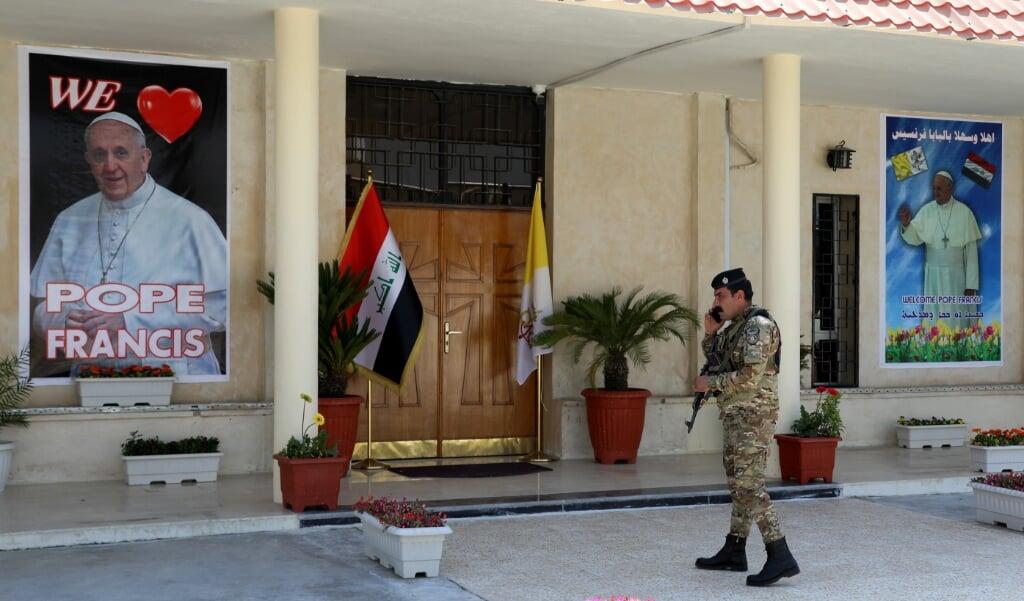 Een Iraakse politieman beveiligt de Chaldeeuws-katholieke Sint-Jozefkerk in Bagdad. Paus Franciscus zal de kerk, waar enkele jaren geleden 48 doden vielen door een aanslag, volgende week bezoeken.   (beeld Epa / Ahmed Jalil)
