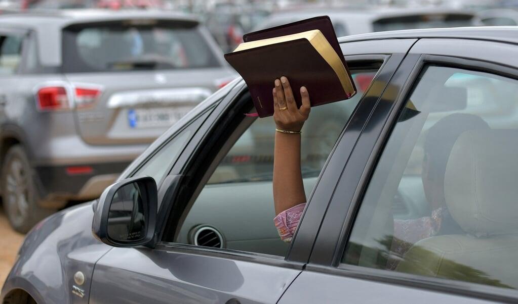 Een vrouw houdt haar Bijbel in de lucht tijdens een openluchtdienst van Bethel Church. Paul Pressler was jeugdleider van de bekende kerk.  (beeld Manjunath Kiran / afp)