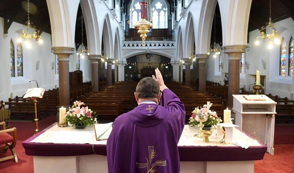 Een priester gaat voor in de eucharistie in een lege kerk in Dublin.  (beeld EPA / Aidan Crawley)