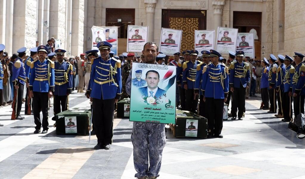 Een pro-Houthi millitant houdt een portret vast van een Houthistrijder die is omgekomen in de opgelaaide gevechten.  (beeld epa / Yahya Arhab)