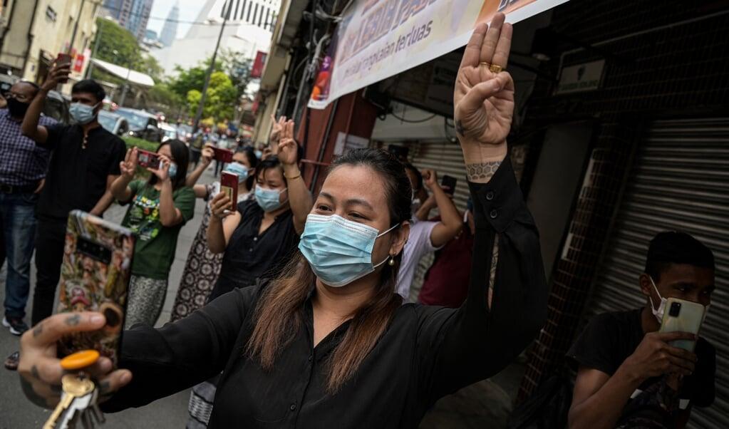Een vrouw in Kuala Lumpur, aanhanger van de Nationale Liga voor Democratie in Myanmar, geeft een groet als statement tegen de militaire coup in Myanmar.  (beeld afp / Mohd Rasfan )