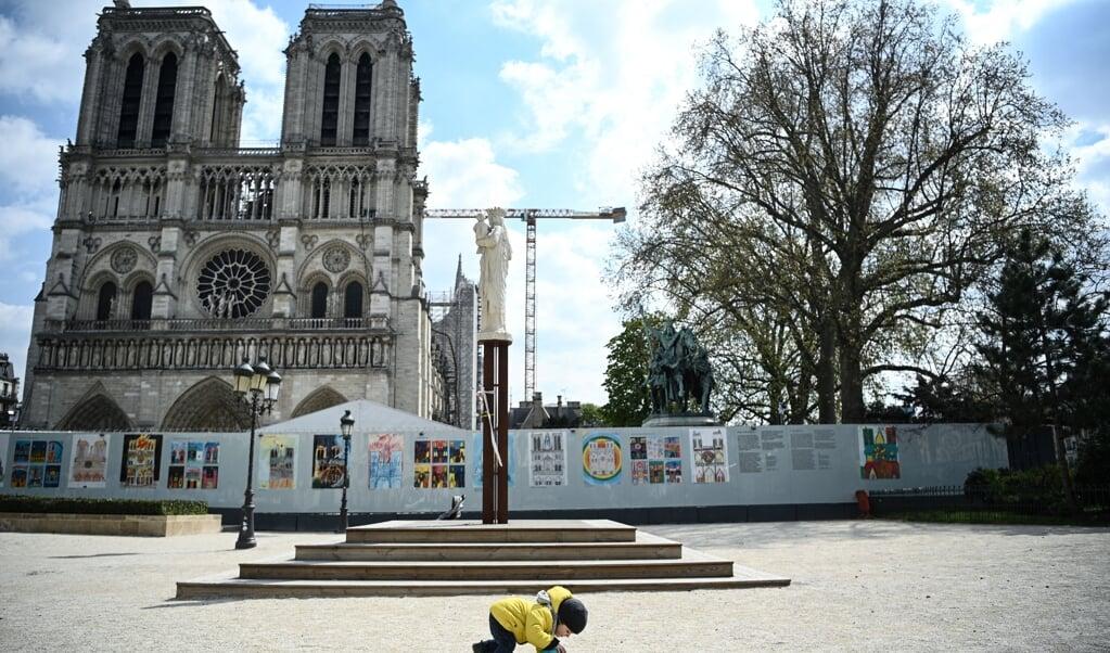 Een kind speelt met een bal op het plein voor de Notre Dame.  (beeld afp / Anne-Christine Poujoulat)