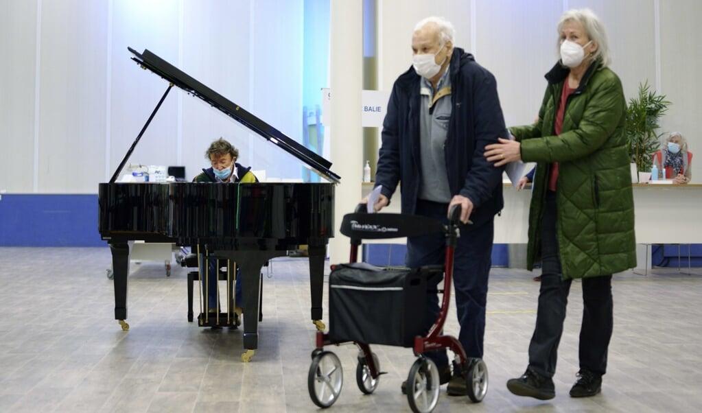 Bezoekers van een vaccinatielocatie in Leiden vielen afgelopen weekend opeens in een pianoconcert van Laurens van Rooyen, bedoeld als steun voor alle GGD- en Rode Kruis-medewerkers die hulp bieden bij het vaccineren.  (beeld epa / Phil Nijhuis)