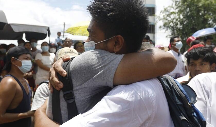 Activist Zayar Lwin begroet een vriend, nadat hij is vrijgelaten uit de gevangenis in Yangon.  (beeld epa)