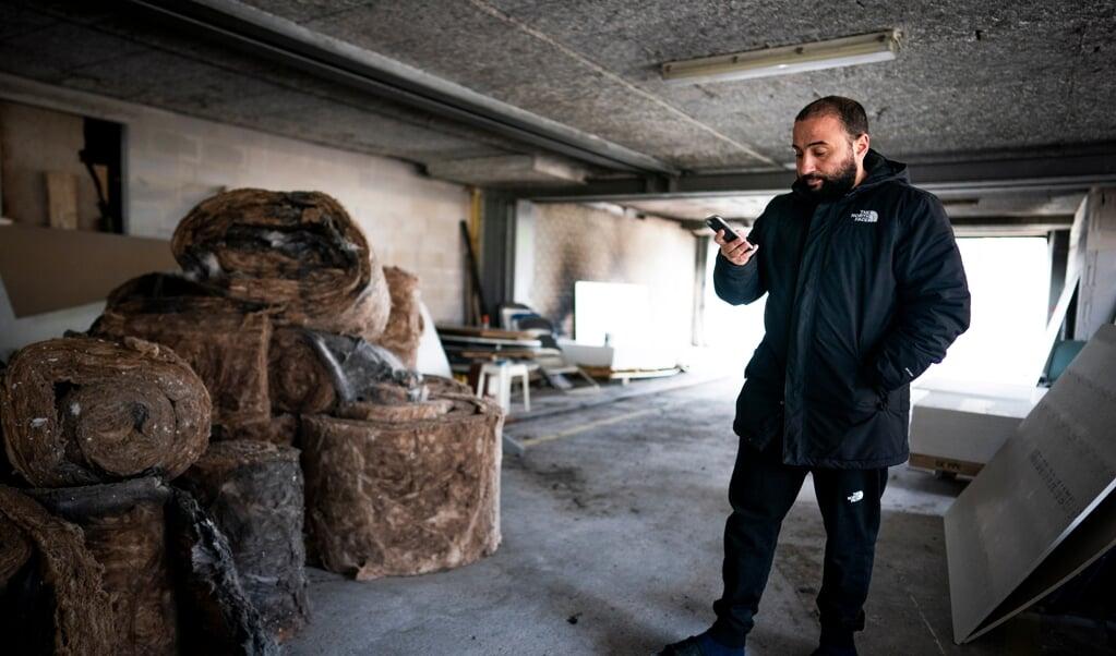 Fouad Khouakhi kijkt op zijn telefoon naar reacties op de brand in de moskee in Gouda.   (beeld Freek van den Bergh)