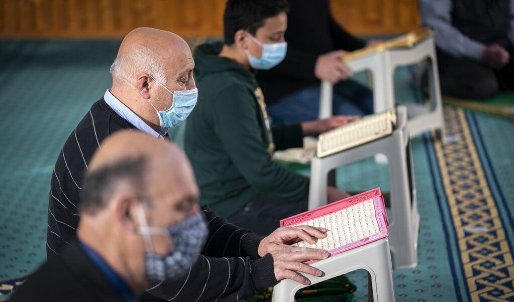 Enkele mannen reciteren de Koran in de Hilversumse Mevlana Moskee. Tijdens de Ramadan gebeurt dat grotendeels digitaal.  (beeld anp / Jeroen Jumelet)