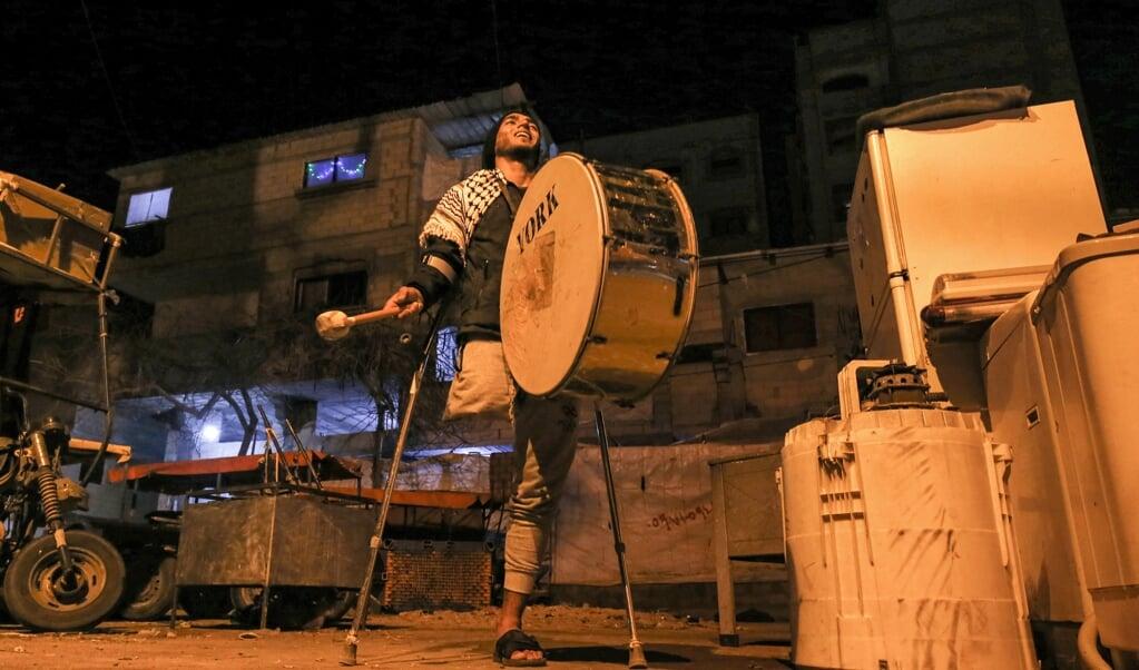 Een 'ramadan drummer' gaat door de straten in Rafah om de vastende moslims te wekken voor het ontbijt vóór zonsopgang.   (beeld afp / Said Khatib)