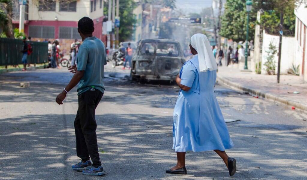 Na een eucharistieviering op woensdag 15 april braken gewelddadigheden uit rond de Sint-Pieterskerk in Port-au-Prince. Bisschoppen vierden de mis om te bidden voor tien gegijzelden, waaronder vijf priesters en twee vrouwelijke religieuzen.   (beeld Epa/Jean Marc Herve Abelard)