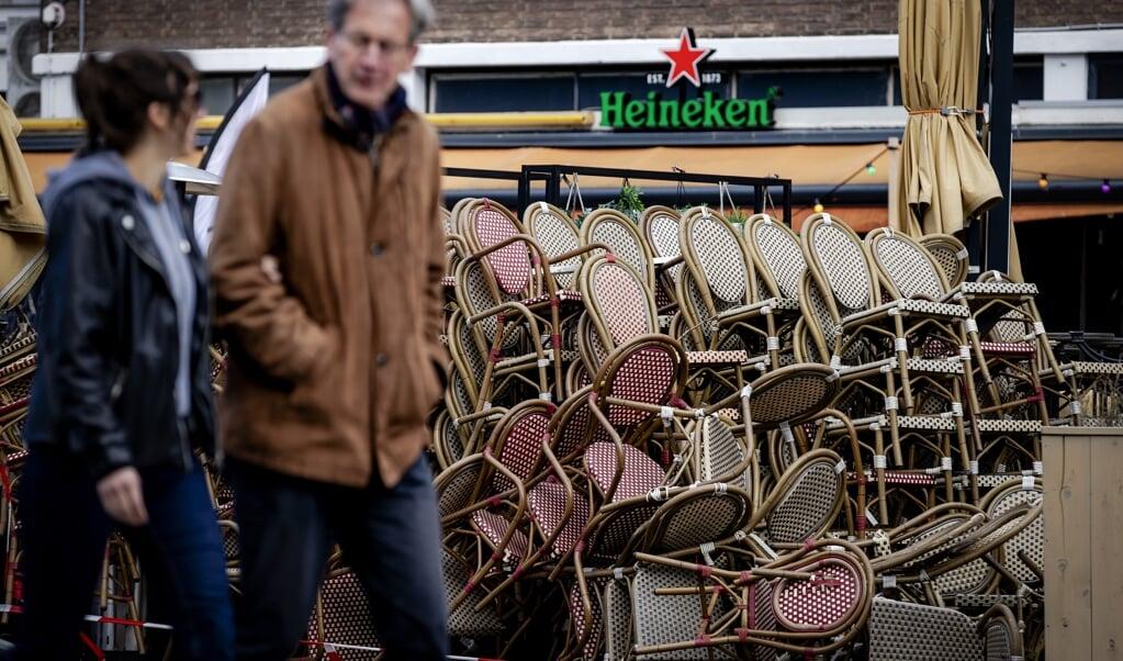 Stoelen en tafels van een terras staan opgestapeld in Rotterdam.  (beeld anp / Robin van Lonkhuijsen)