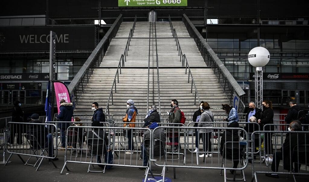 Wachten in de rij voor een prik in het Stade de France in Saint-Denis. Hoe meer mensen al zijn ingeënt, des te sterker de bereidheid toeneemt, denkt de regering.  (beeld afp / Christophe Archambault)