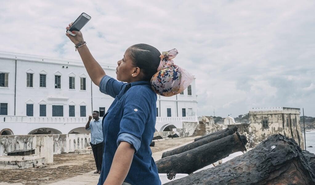 Een Amerikaanse toerist bezoekt het beruchte Cape Coast Castle in Ghana. Hier vertrok ruim vierhonderd jaar geleden het eerste slavenschip richting Virginia in de Verenigde Staten.   (beeld Natalija Gormalova / AFP)