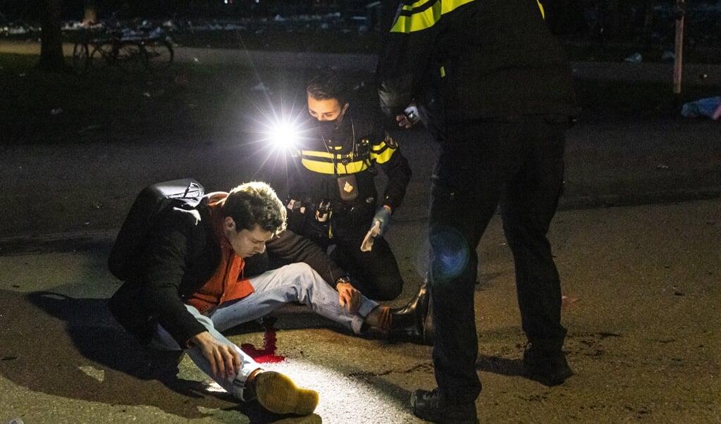 Februari dit jaar: politieagenten helpen een bezoeker die in het Vondelpark op zijn achterhoofd is geraakt door een fles. Echte leiders, 'leiders van hoop', zijn bijvoorbeeld leraren, agenten, verpleegkundigen met oog voor kwetsbaren.  (beeld anp / Dingena Mol)