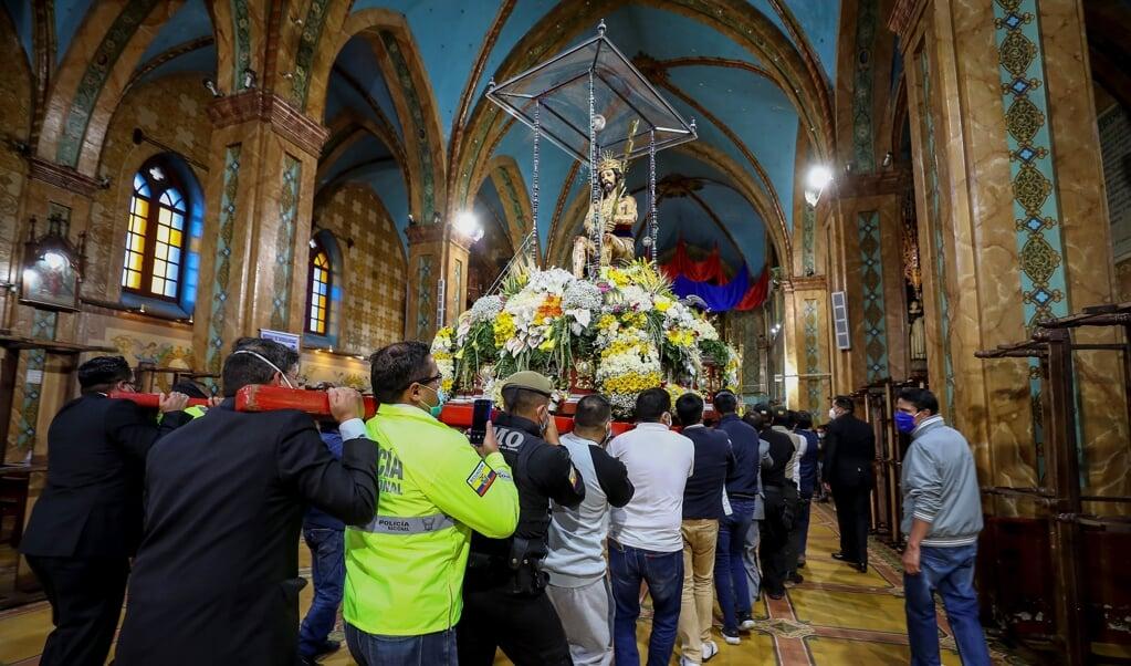 Een Jezusbeeld wordt tijdens een rooms-katholieke processie door een kerk in Riobamba gedragen.   (beeld Epa / Jose Jacome)