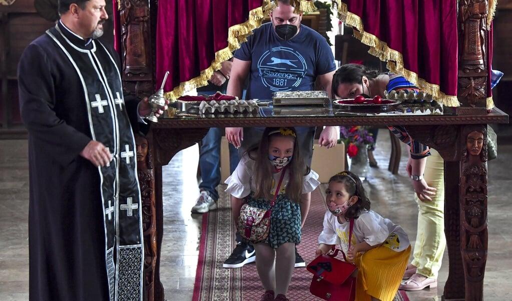 Noord-Macedonische kinderen kruipen tijdens de orthodoxe Goede Vrijdagviering onder een tafel door, die het graf van Jezus symboliseert.   (beeld epa / Georgi Licovski)