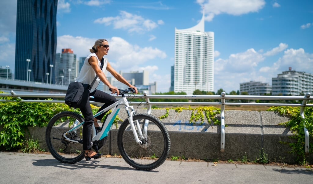 side view happy smiling 45 years old business woman cycling on electric bicycle outdoors on sunny summer day in european city, office buildings blurred in background  (beeld istock)