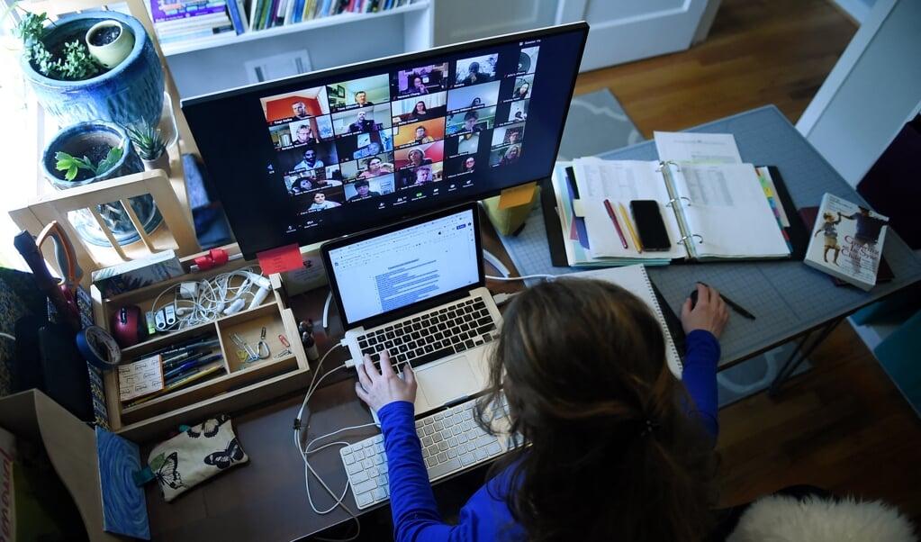 Dag in dag uit uren achter de webcam, het is een gebruikelijk beeld geworden het afgelopen jaar.  (beeld afp / Olivier Douliery)