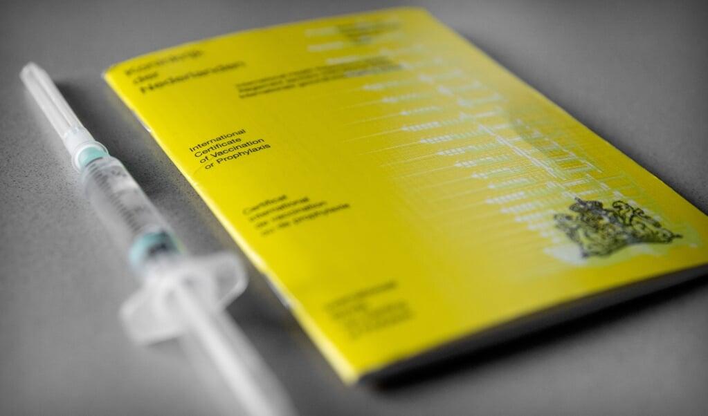 Een geel vaccinatieboekje waarin iemands vaccinaties staan geregistreerd. Het kabinet werkt aan een vaccinatiepaspoort waarmee bezoekers van evenementen straks bij de ingang kunnen laten zien dat dat zij tegen COVID-19 gevaccineerd zijn.  (beeld anp / Koen van Weel)