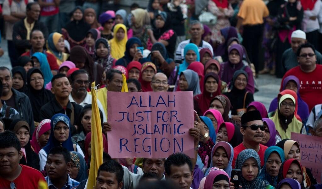 In Maleisië wordt al jarenlang gepraat over de vraag of de roomskatholieke kerk de term 'Allah' voor God mag gebruiken. Beeld: islamitische actievoerders in 2014 voor het Hooggerechtshof in Kuala Lumpur.  (beeld afp Photo / Manan Vatsyayana Manan Vatsyayana / afp)