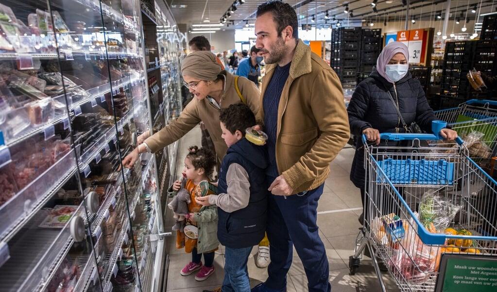 Fatima Llouh en Rachid Lamrabat, het stel achter By Oummi, met hun kinderen bij een AH in België.  (beeld Arie Kievit)