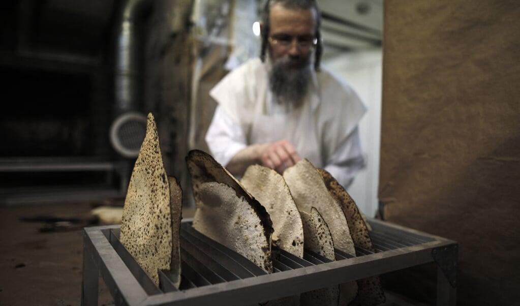 Het bakken van matzes (platte broden) tijdens pesach in Jeruzalem.  (beeld afp / Menahem Kahana)