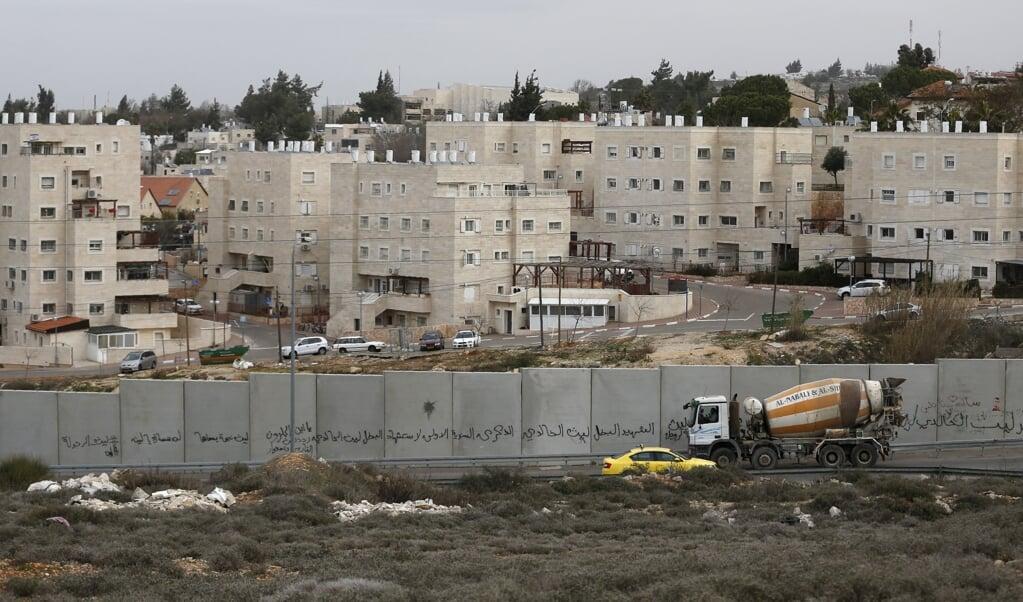 Een muur scheidt de Israëlische nederzetting Beit El van de Palestijnse hoofdstad Ramallah.  (beeld afp Abbas Momani)