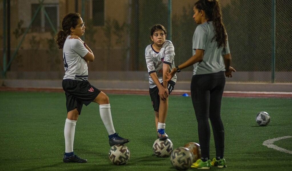 Farida Salem tijdens de training in gesprek met Nour (l) en Sarah. 'Ik geef ze veel adviezen, ze kijken tegen me op.'  (beeld René Clement)