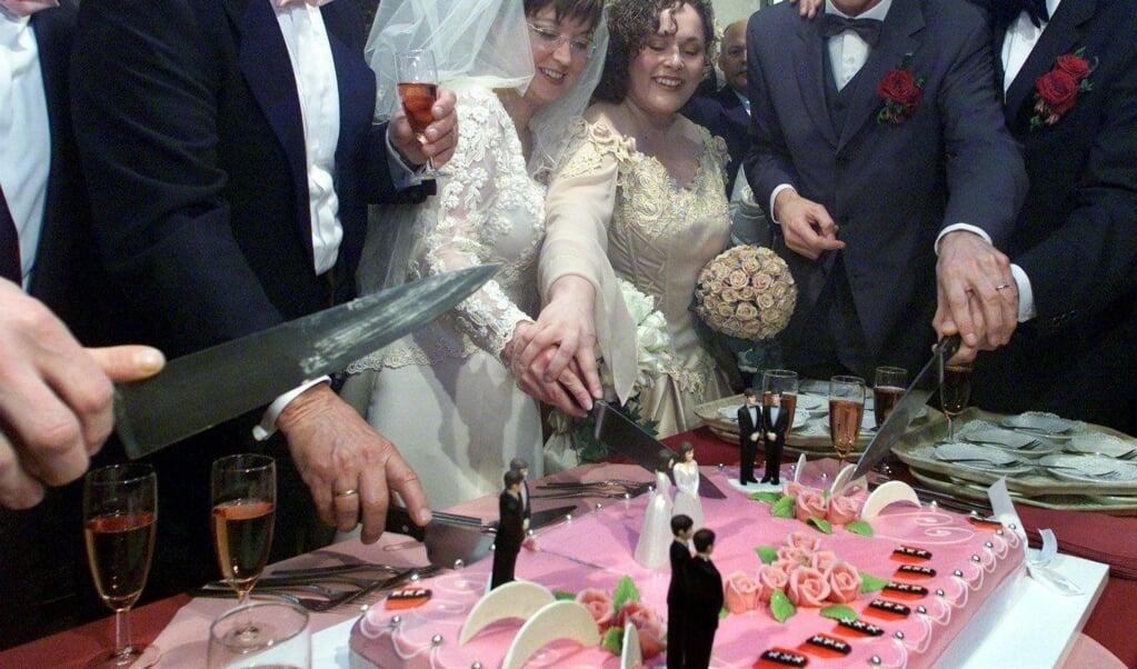 Echtparen snijden op 1 april 2001 de bruidstaart aan nadat zij officieel in het huwelijk zijn getreden.  (beeld anp / Marcel Antonisse)