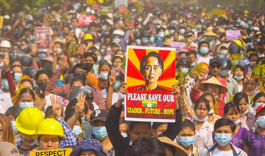 Een demonstrant houdt tijdens een protest tegen de militaire coup in Myanmar een poster met daarop een foto van Aung San Suu Kyi omhoog.   (beeld afp)