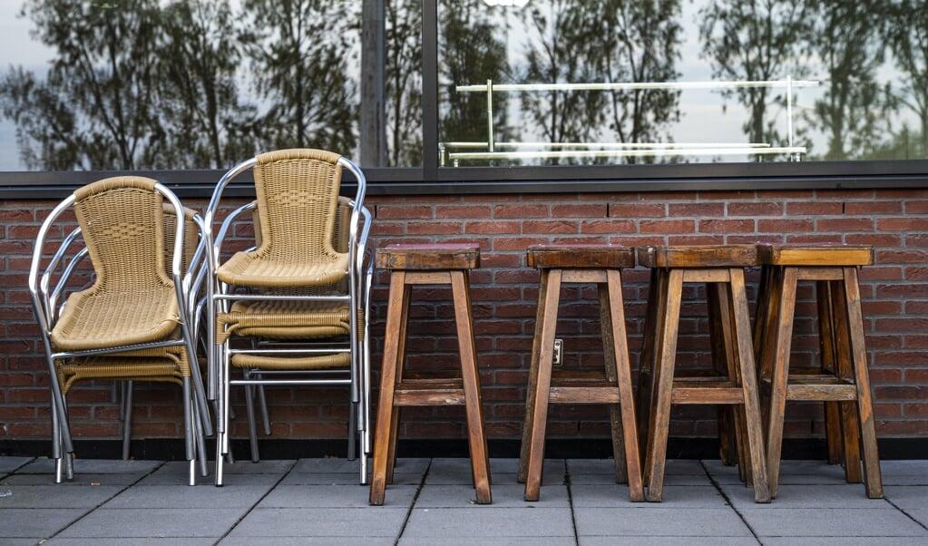 Barkrukken stoelen staan opgestapeld op het terras van voetbalvereniging Olympia in Gouda.   (beeld anp / Tobias Kleuver)