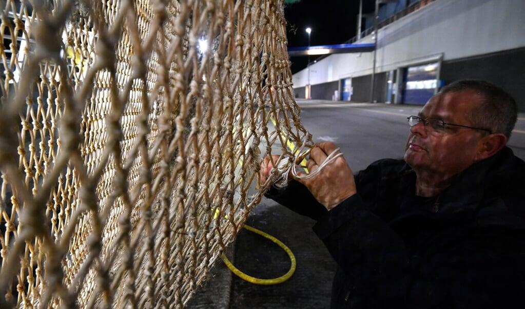 Een Texelse visser repareert een elektrisch pulsnet, nadat hij zijn vangst in de haven van Den Helder heeft gelost.  (beeld afp / Emmanuel Dunand)